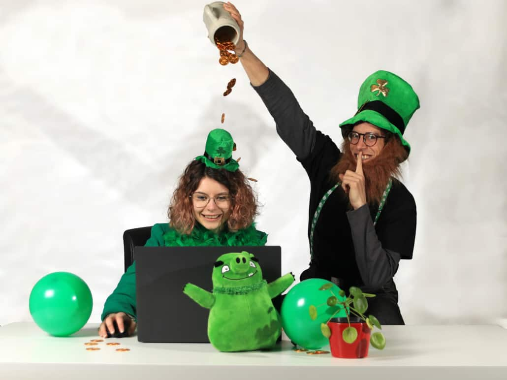 Man in St. Patrick's day costume pooring coins out of a mug on top of a girl in green costume before laptop
