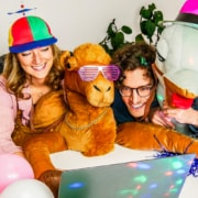 Two People infront of Laptop with funny costumes doing online team building games